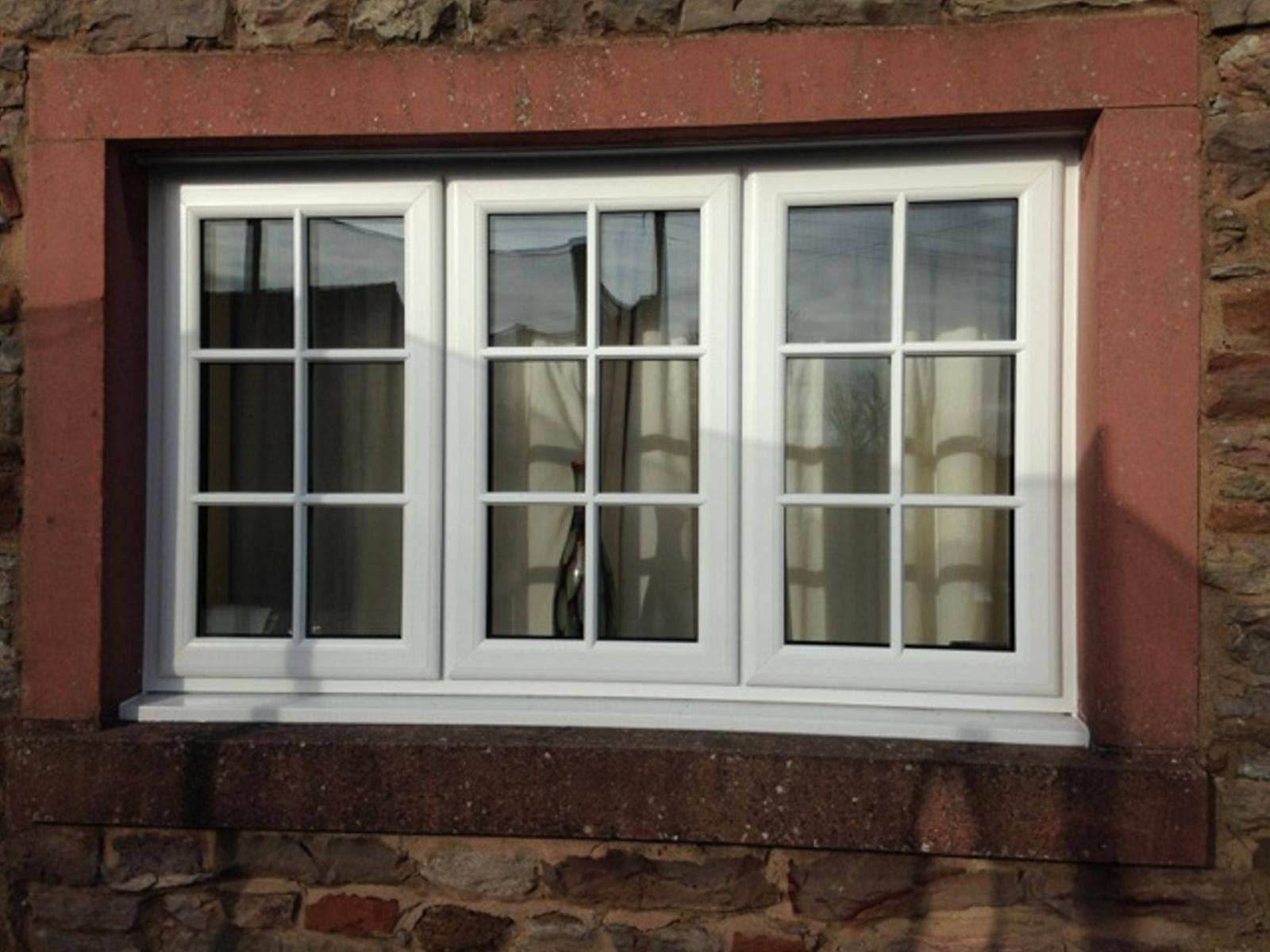 White PVC window - equal glass sizes with central dummy sash and 2 side openers - glazed with face-fix bars